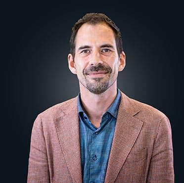 Portrait des geschäftsführenden Gesellschafter Gerhard Nieke. Er trägt einen roten Anzug und ein blaues Hemd. Der Hintergrund ist schwarz.