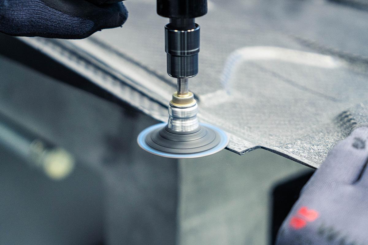 Hände mit Schleifmaschine bearbeiten Material aus Kohlefaser